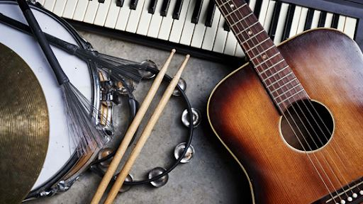 photo of a tambourine, snare drum with drumsticks, a guitar, and electric keyboard shot from above